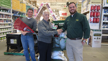 The winner of the Russell Lake Takes Root raffle prize receives his winnings at Kent Building Supplies Russell Lake